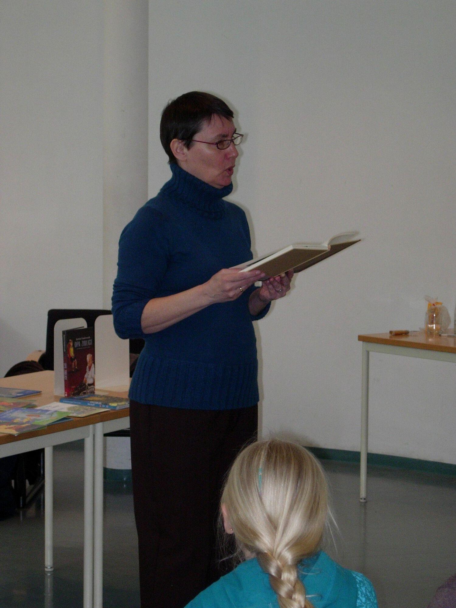 Katrien Van de Woude op bezoek in de bib van Merelbeke.